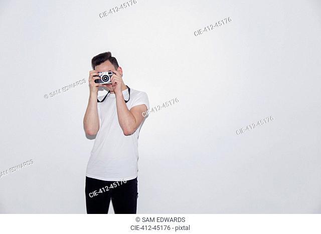 Teenage boy using retro camera
