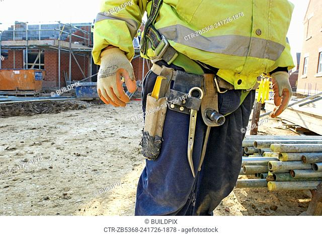 Worker with Toolbelt on a housing development site under construction, South East England, UK