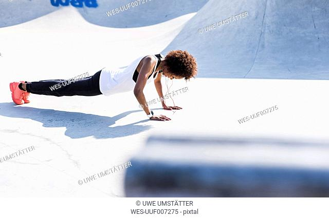 Young woman doing pushups in skatepark