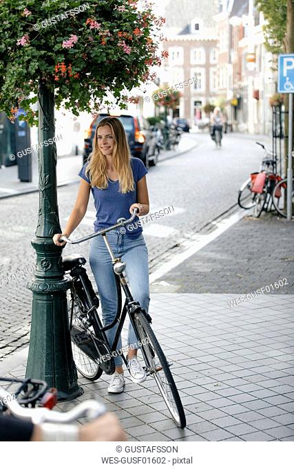 Netherlands, Maastricht, young woman with bicycle in the city