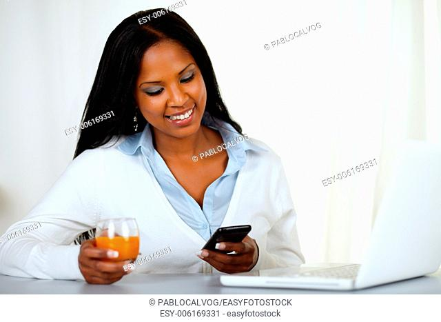 Portrait of a young woman sending a message by the mobile at home indoor