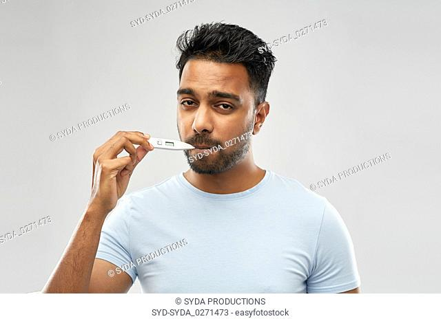 man measuring oral temperature by thermometer