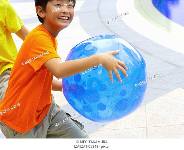 Portrait of a boy holding a ball with his friend at the poolside