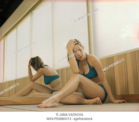 Woman sitting in dance studio, looking fustrated