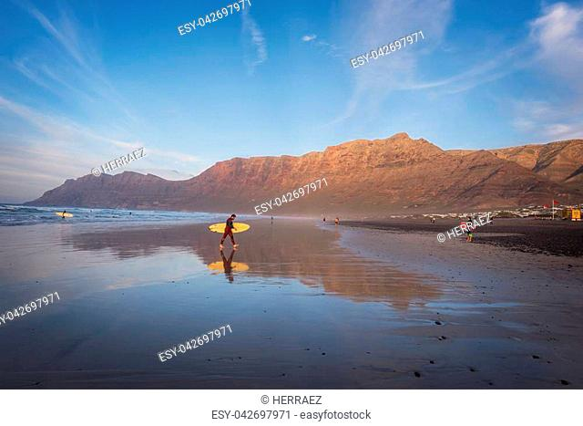 Lanzarote, Spain - February 20, 2018: Surfer in Famara beach in Lanzarote, Canary islands, Spain
