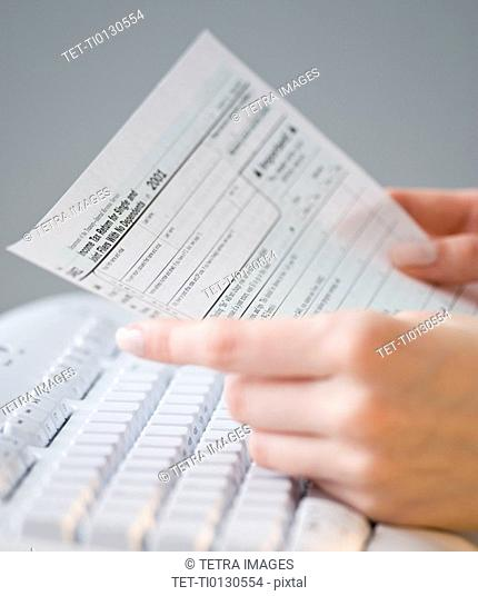 Woman holding tax form over keyboard