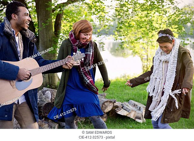 Friends playing guitar and dancing at lakeside campsite
