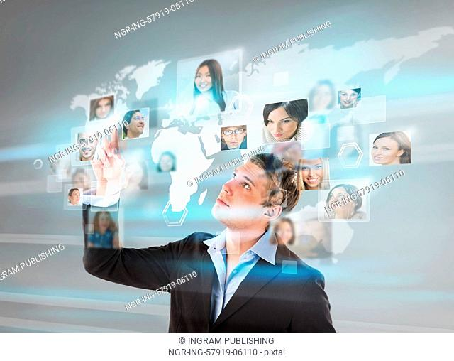 Young successful man looking at worldmap with profile photos of his colleagues and touching virtual screen. International communication concept