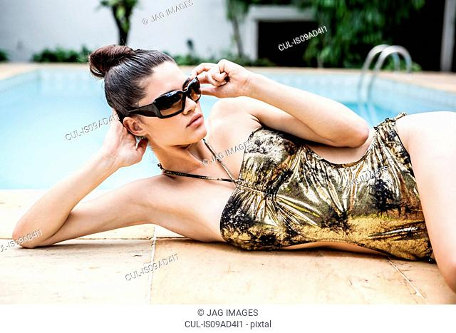 Young woman in gold bathing costume at hotel poolside