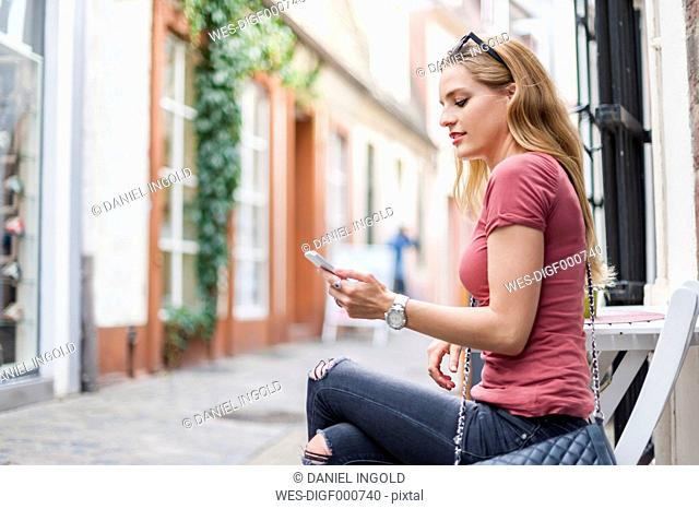 Young woman sitting at sidewalk cafe looking at her smartphone