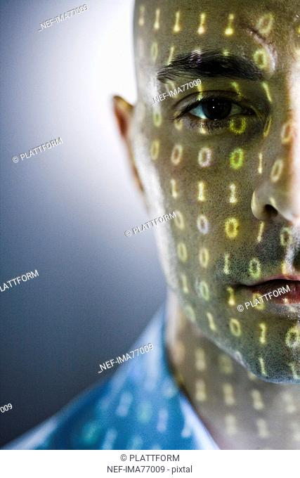 Close-up of a man with digital numbers reflected on his face