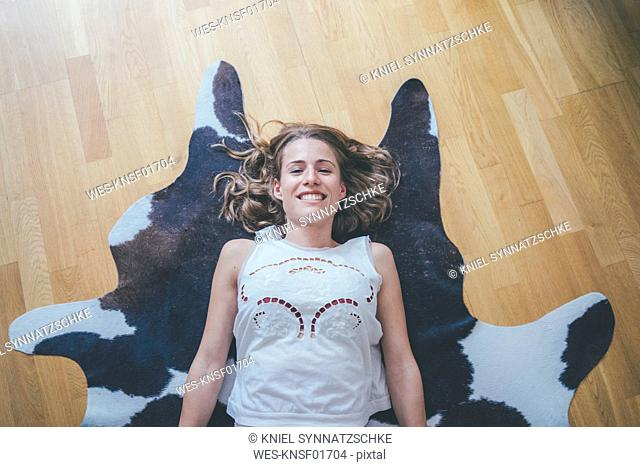 Portrait of smiling young woman lying on fur on the floor