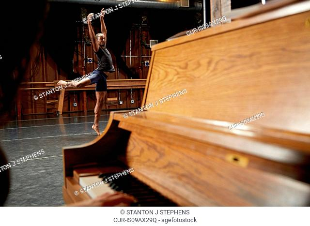 Ballet dancer in position, piano in foreground