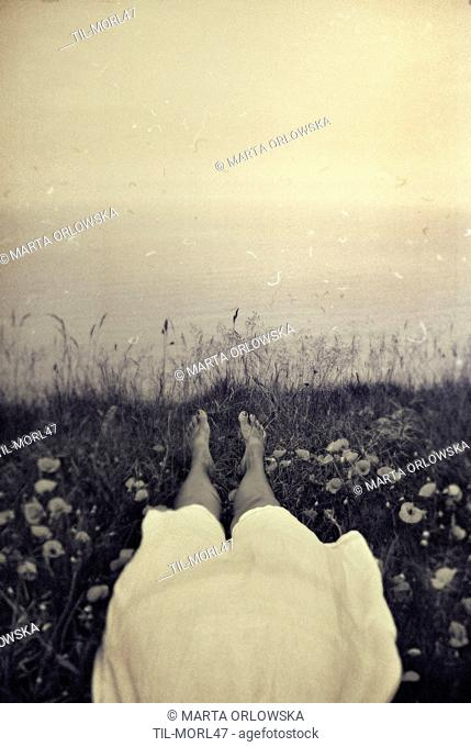 Close up of young woman lying in grass with view out to sea