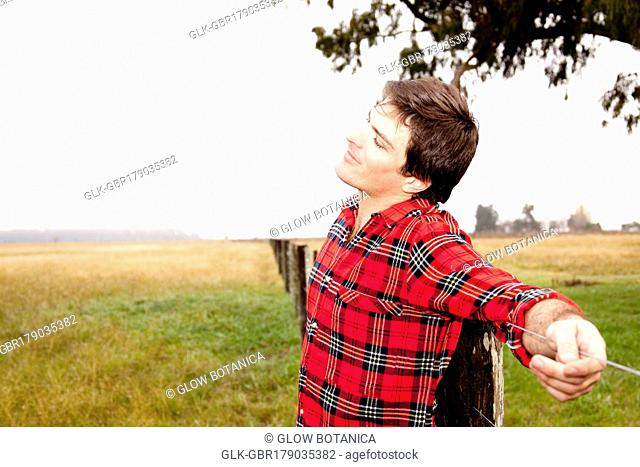 Man leaning against a fence in a field