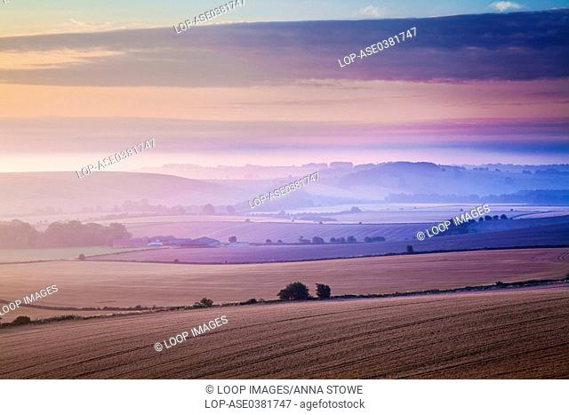 A midsummer dawn view over the Marlborough Downs in Wiltshire from Liddington Hill