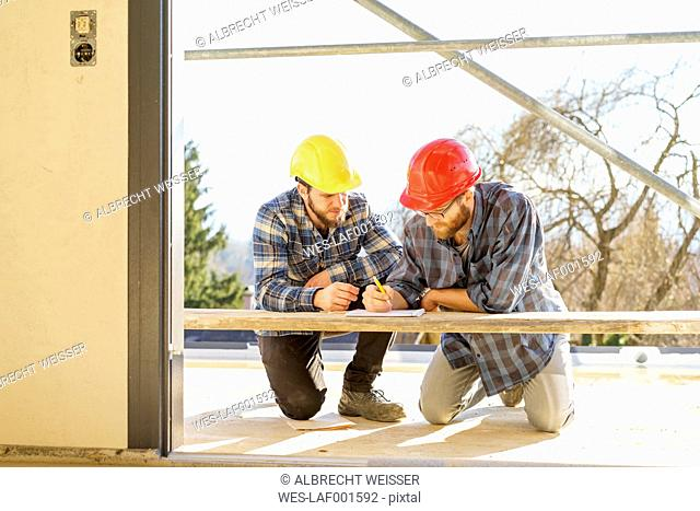 Two craftsmen discussing and taking notes in construction site