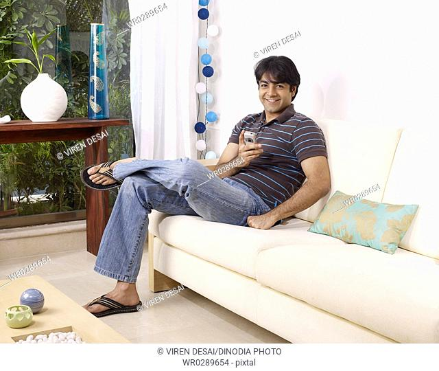 Young man holding mobile sitting on sofa MR702V