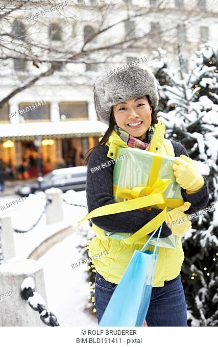 Korean woman with gifts walking in snow