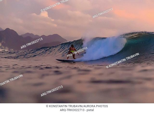 Rear view shot of female surfer in bikini riding wave at sunset