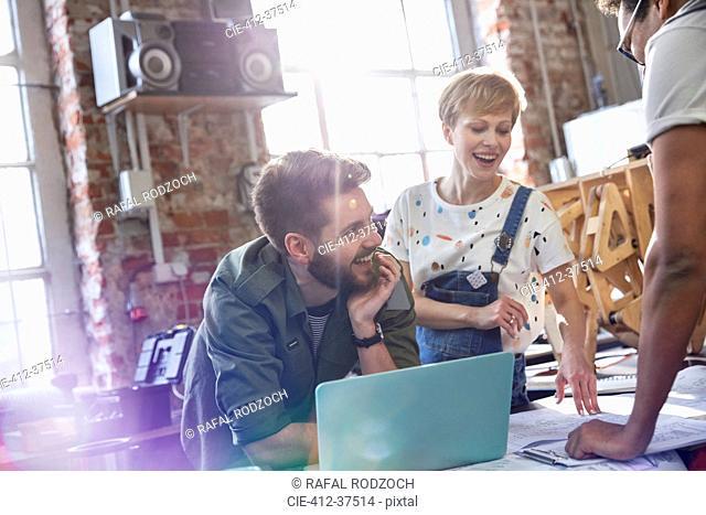 Smiling designers meeting at laptop in workshop
