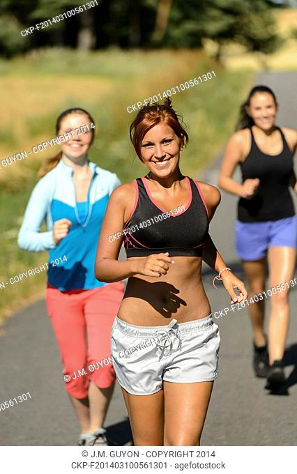 Friends jogging together outdoors sunny path smiling