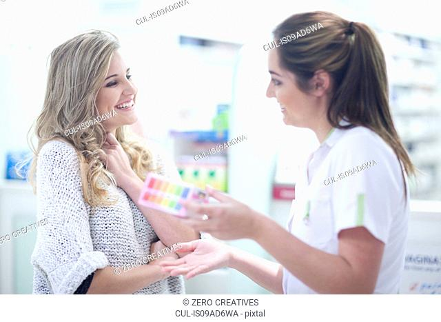 Young woman talking to pharmacist