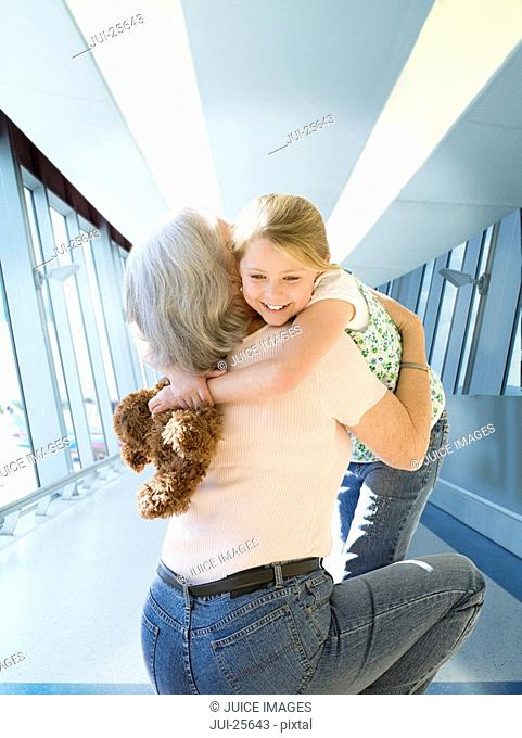 Grandmother greeting and hugging granddaughter at airport