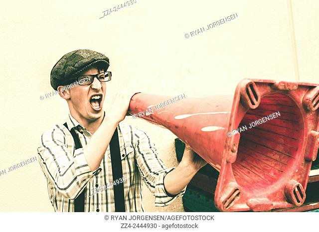 Comical retro portrait of insane young man shouting out a call to attention through a road marker loud hailer. Communication concept