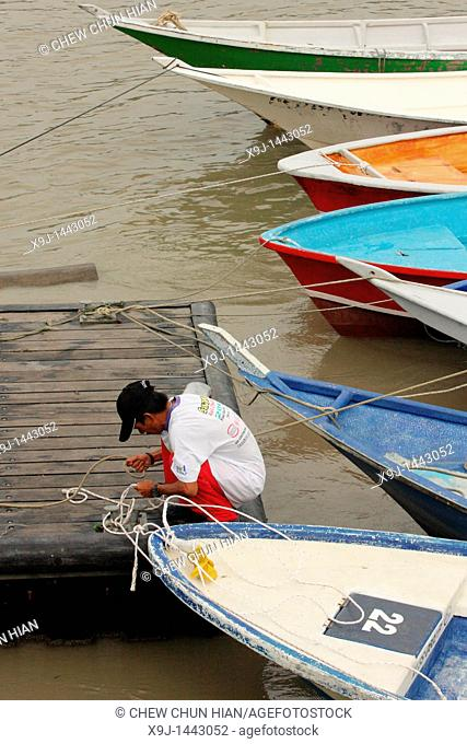 man tying rope at wooden jetty