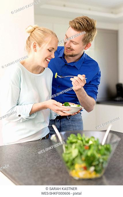 Happy couple in kitchen with salad