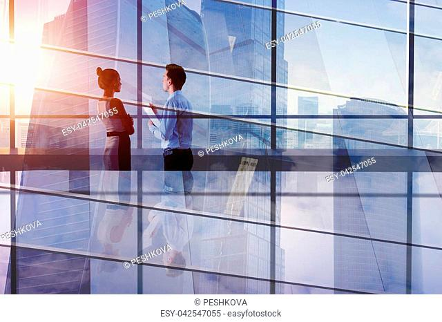 Businesspeople in abstract office interior with city view. Teamwork and finance concept. Double exposure