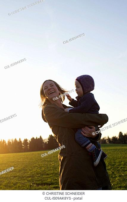 Mature mother and baby daughter laughing in field at sunset