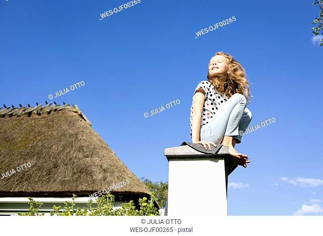 Girl sitting on a wall under blue sky