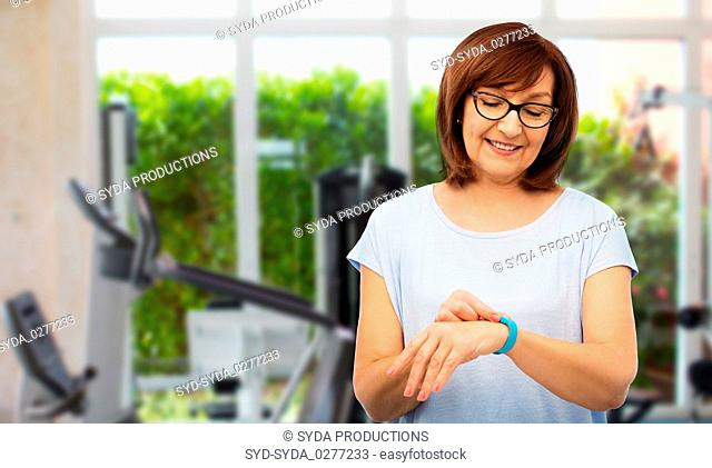 smiling senior woman with fitness tracker in gym