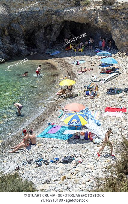 Sunbathers on a pebble beach in a small bay on the island of Tabarca Spain