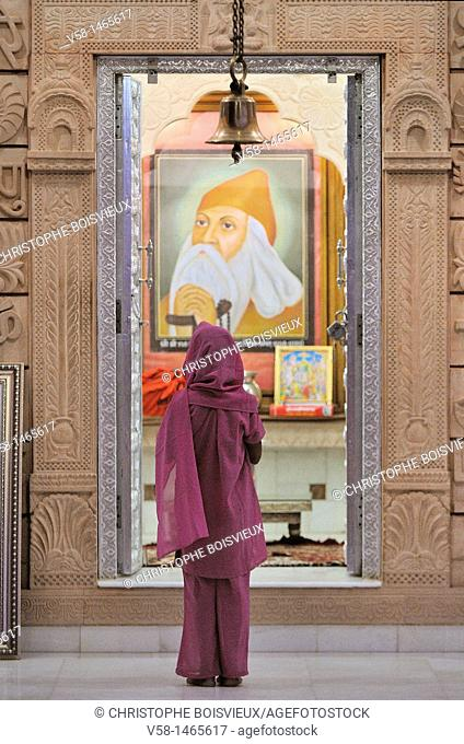Bishnoi devotee in prayer before the portrait of Guru Jambeshwar, Jodhpur region, Rajasthan, India