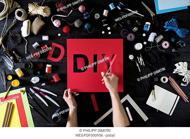 Man's hands cutting out the word DIY of red cardboard