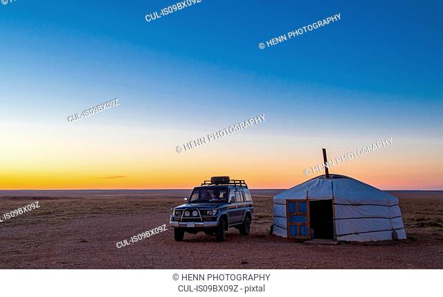 Off road vehicle parked by ger or yurt camp, Gobi desert, Mongolia