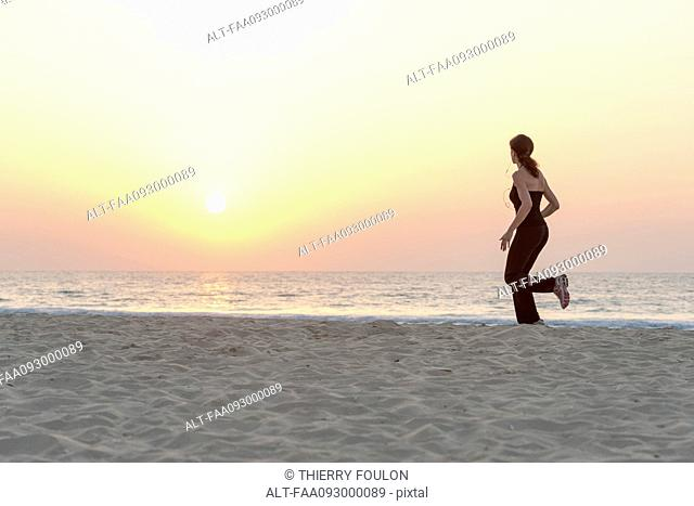 Woman jogging on beach at sunrise