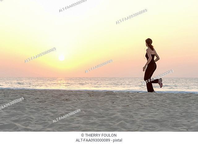 Woman jogging on beach at sunrise