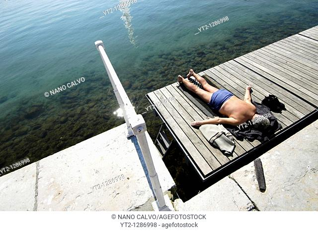 An elderly man taking a sunbath in Bains des Paquis, in Geneva, Switzerland