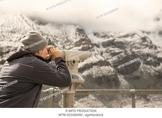 Mature man looking at view with telescope, Grossglockner mountain with Glacier Pasterze, National Park Hohe Tauern, Carinthia, Austria