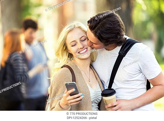 A young man kisses a young woman on the cheek while she is checking social media on a smart phone on a university campus; Edmonton, Alberta, Canada