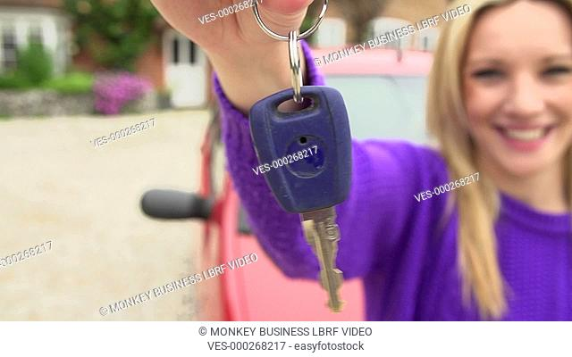Happy teenage girl holds out key to car in slow motion sequence.Shot on Sony FS700 in PAL format at a frame rate of 200fps