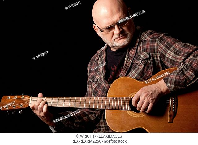 Senior Man playing acoustic Guitar, Munich, Germany
