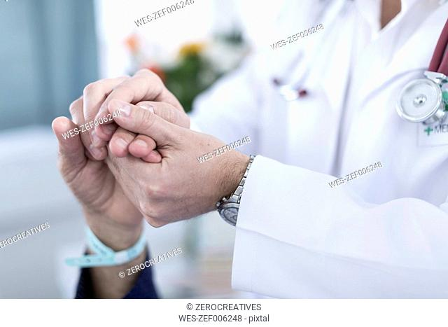 Doctor holding patient's hand, close-up