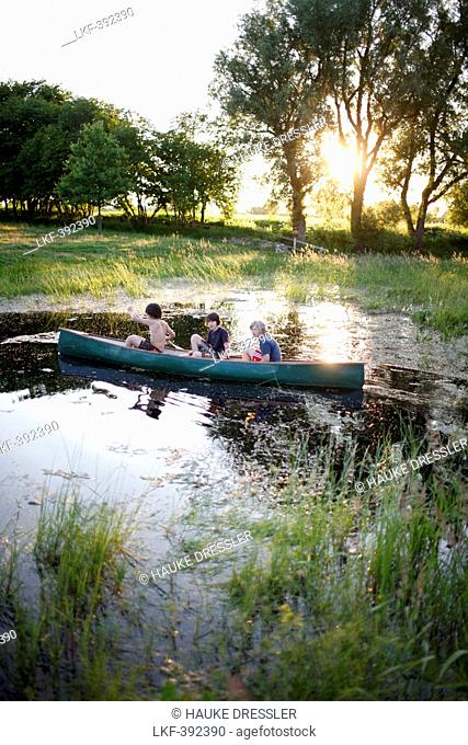 Three boys in a canoe on a pond, Klein Thurow, Roggendorf, Mecklenburg-Western Pomerania, Germany
