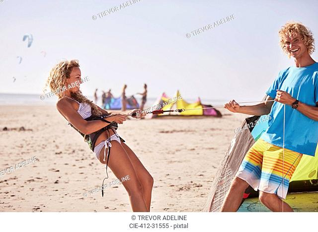 Playful couple preparing kiteboarding equipment on sunny beach