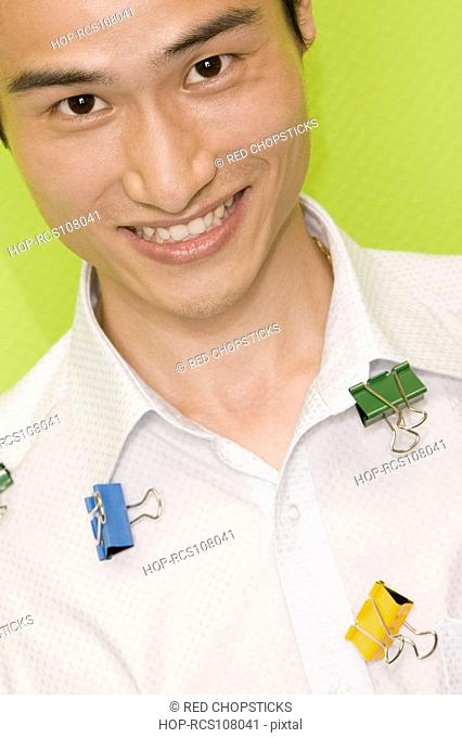 Portrait of a young man with paper clips on his shirt